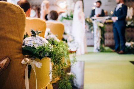 Wedding ceremony area, flowers composition with greenery and ribbons on the yellow chairs, bride and a groom on a background