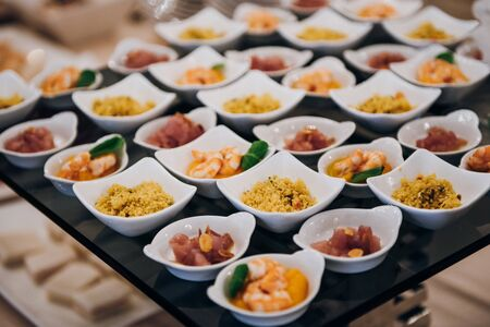 snacks in small ceramic bowls on the buffet table, there are couscous, shrimp, meat