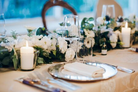 Wedding table decorated with tablecloth, fresh flowers composition, candles, plates with napkins and glasses