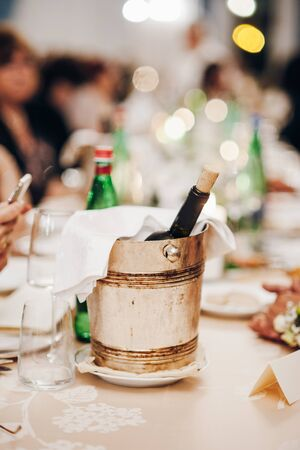 A champagne bucket is on the festive table, on top is a white cloth napkin Standard-Bild