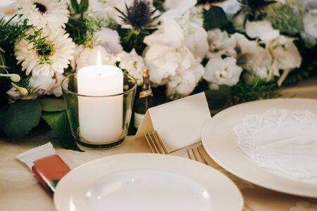 Festive table decorated with fresh flowers, candles, plates, forks and empty cards
