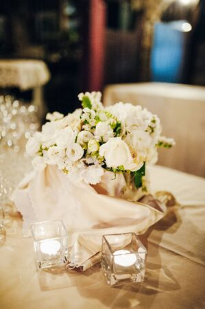 composition of white flowers are on the table decorated with candles and tablecloth with napkins Standard-Bild