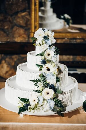 Four tiered white wedding cake decorated with fresh flowers standing on the table