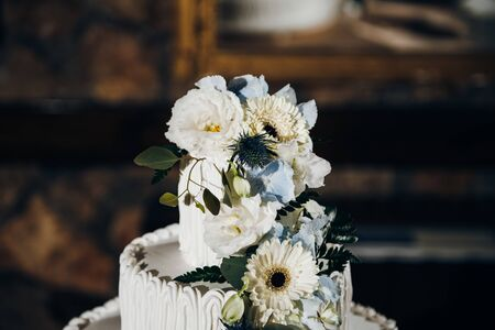 Top of the wedding cake with white cream and fresh flowers