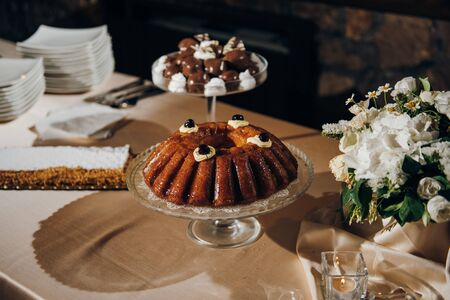 Traditional italian rum baba is on the table, there are other desserts and fresh flowers on the table