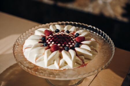 Vanilla panna cotta decorated with berries and red sauce is on the cake stand