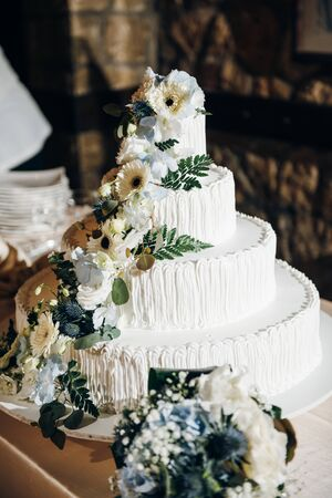 White wedding four tier cake decorated with fresh flowers and greenery Standard-Bild