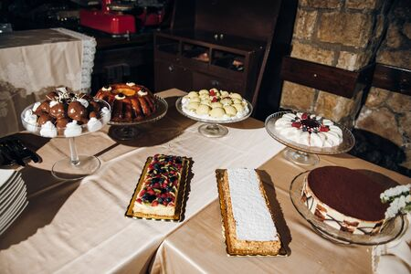 Delicious cakes and desserts are on the table, decorated with fresh berries, chocolate, cream