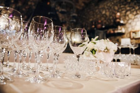 Empty wine glasses are standing on a table covere with tablecloth, there are white flowers on the background Standard-Bild