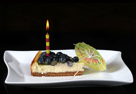 delicious slice of blueberry cheesecake with burning candle