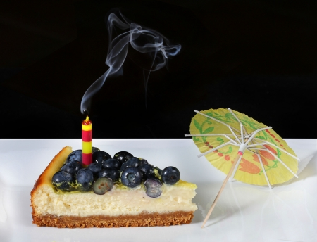 delicious slice of blueberry cheesecake with extinguished candle