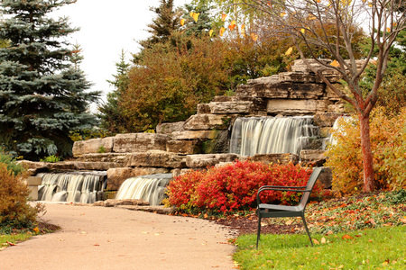 Park bench and waterfall in autumn park Stock Photo