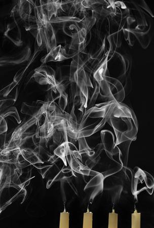 Extinguished candles with smoke on black background Stock Photo
