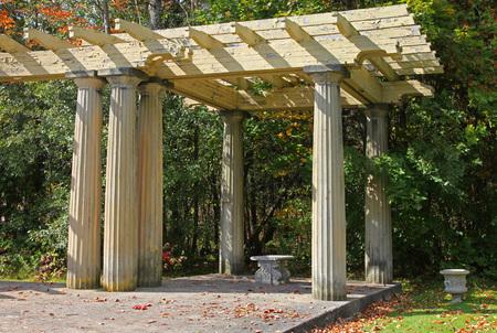 Old shaded arbor and Elegant stone bench in Seneca park. Stock Photo
