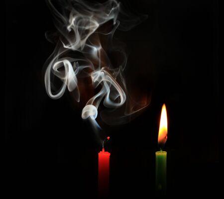 burning and extinguished candles on black background Stock Photo