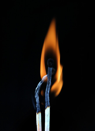 ignited: Two burning match on black background