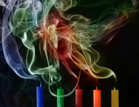 Extinguished candles with colorful smoke on black background