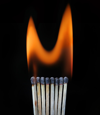 sequential: Burning row of matches against black Stock Photo