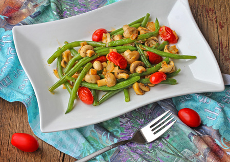 Green beans with mushrooms and tomatoes on a plate.