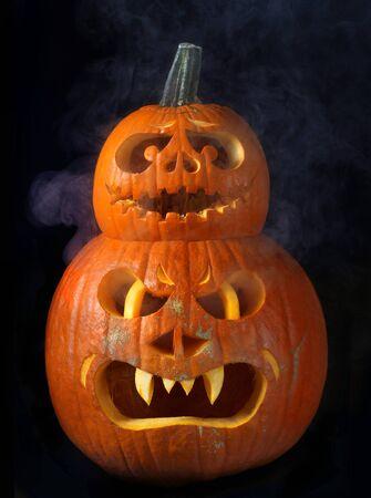 Scary Halloween pumpkins Jack O Lanterns isolated on black background with smoke