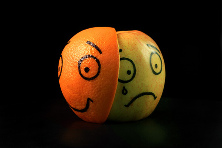 sad apple with happy orange mask on black background