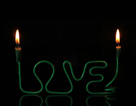 love candle holder made from wire with two burning candles