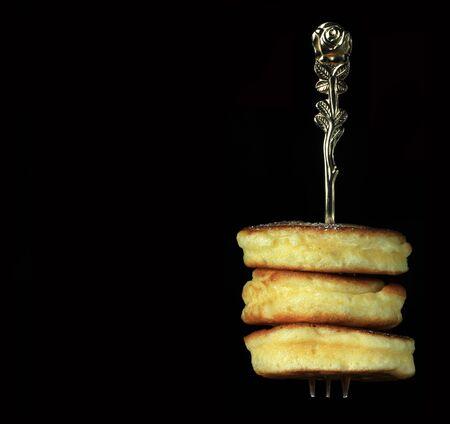 Freshly baked mini pancakes on fork against black background Фото со стока