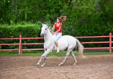A girl riding a horse bareback
