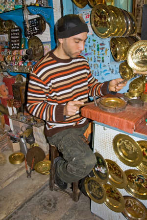 TUNIS - DECEMBER 04  An unidentified Workman works on a souvenir in the medina on December 04, 2009 in Tunis  The medina has a lot of tiny crafts shops
