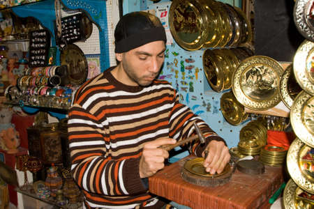 gold souk: TUNIS - DECEMBER 04  An unidentified Workman pounds on a souvenir in the medina on December 04, 2009 in Tunis