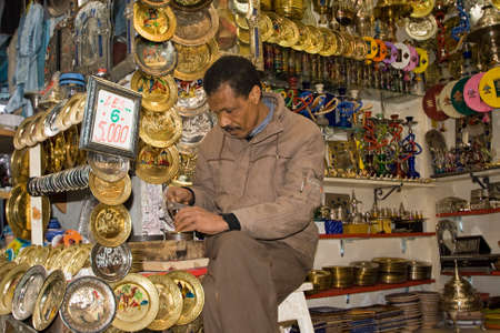 TUNIS - DECEMBER 04  An unidentified Workman works on a souvenir in the medina on December 04, 2009 in Tunis   The medina has a lot of tiny crafts shops  Stock Photo - 13140624