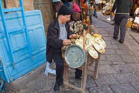 TUNIS - DECEMBER 04  An unidentified Workman works on a souvenir in the medina on December 04, 2009 in Tunis   The medina has a lot of tiny crafts shops  Stock Photo - 13140619