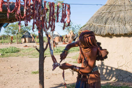Himba Woman cuts Meat Stock Photo