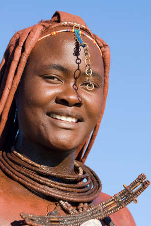 Himba woman portrait with traditional jewelry on blue sky background photo