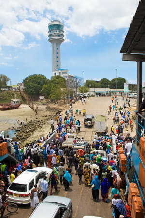 DAR ES SALAAM, TANZANIA - SEPTEMBER 20: A crowed of unidentified people and cars leave the KivukoniKigamboni ferry on September 20, 2012 in Dar es Salaam. Ferry cross from Kigamboni, which is on the south side of the harbour to Kivukoni Front in Dar es S