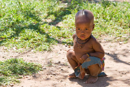 nomad: Cute Himba boy sitting in shade and looking away