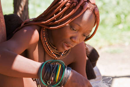 native african ethnicity: Beautiful Himba woman working while singing