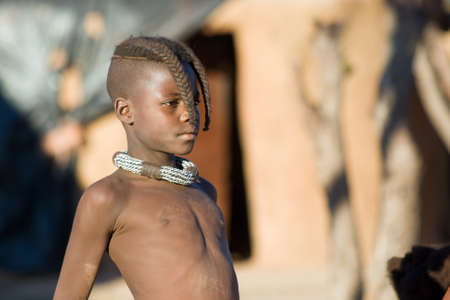 Closeup portrait of proud Himba boy looking away in front of a hut  photo