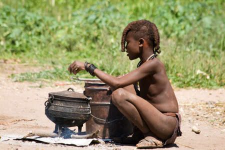 african tribe: Himba boy cooks for lunch