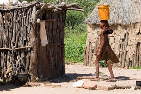 Young Himba woman carries a bucket of water on her head in the middle of the himba village  photo
