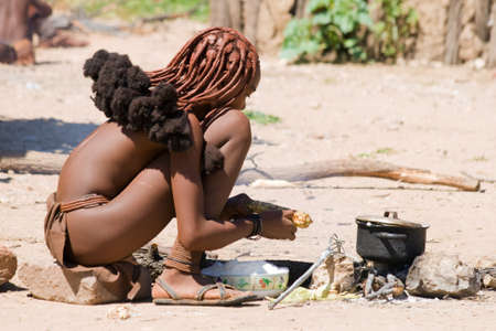 Young Himba woman cooks for lunch