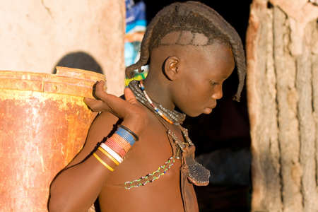 namibia: Himba boy with traditional hair style and jewelry carrying a bucket