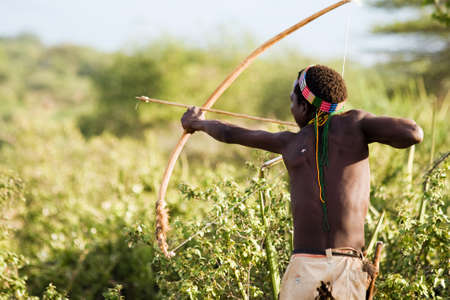 LAKE EYASI, TANZANIA - FEBRUARY 18  An unidentified Hazabe bushman with bow and arrow during hunting on February 18, 2013 in Tanzania  Hazabe tribe threatened by extinction