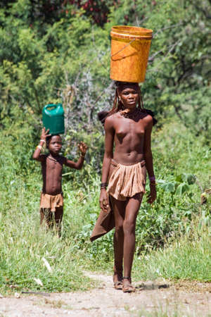 Young Himba woman carries a bucket, Namibia photo