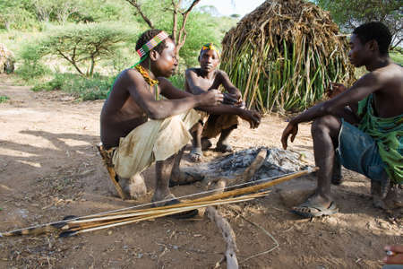 LAKE EYASI, TANZANIA - FEBRUARY 18  A unidentified group of men from Hadza tribe sit around the fire in front of the hut, on February 18, 2013 in Tanzania  Hadzabe tribe threatened by extinction