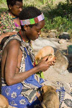 gatherer: LAKE EYASI, TANZANIA - FEBRUARY 18: An unidentified Hadzabe woman sits together with other woman and peels a fruit on February 18, 2013 in Tanzania. Hadzabe tribe threatened by extinction. Editorial