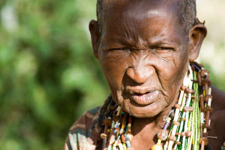 hunter gatherer: LAKE EYASI, TANZANIA - FEBRUARY 18: An unidentified old Hadzabe woman looks seriously in the bush on February 18, 2013 in Tanzania. Hadzabe tribe threatened by extinction. Editorial