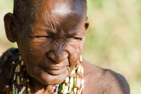 gatherer: LAKE EYASI, TANZANIA - FEBRUARY 18: An unidentified old Hadzabe woman looks seriously at other Hadza people on February 18, 2013 in Tanzania. Hadzabe tribe threatened by extinction. Editorial