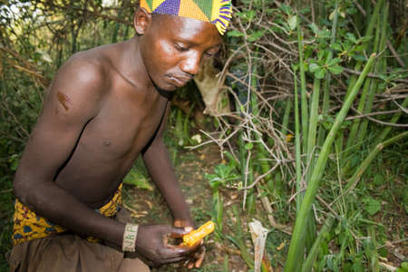 LAKE EYASI, TANZANIA - FEBRUARY 18: An unidentified man from Hadza tribe offers honeycomb in the bush, on February 18, 2013 in Tanzania. Hadzabe tribe threatened by extinction. Editorial