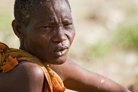 gatherer: LAKE EYASI, TANZANIA - FEBRUARY 18: An unidentified Hadzabe woman looks pensively in the bush on February 18, 2013 in Tanzania. Hadzabe tribe threatened by extinction. Editorial